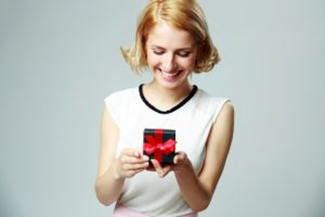 Smiling beautiful young woman holding an open jewelery gift box