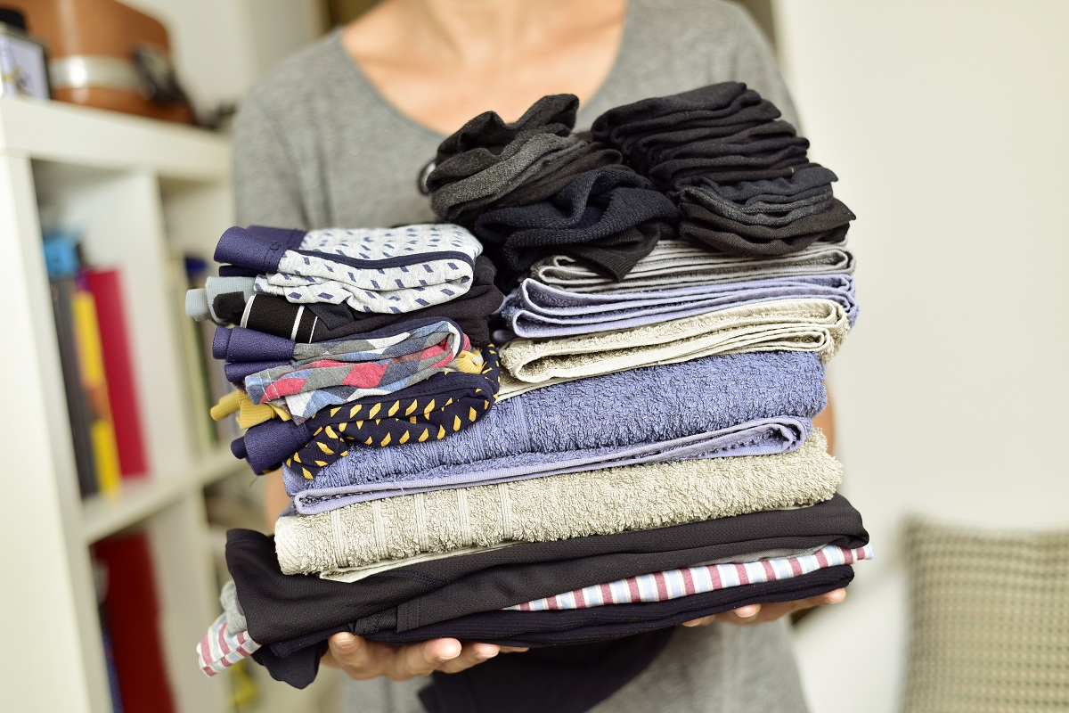 woman holding stack of clothes