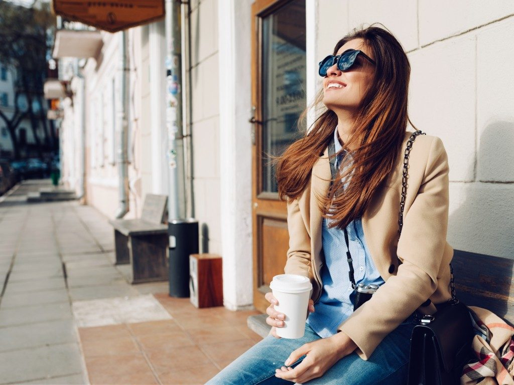 woman wearing sunglasses drinking coffee