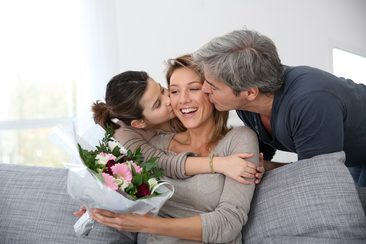 Mother being kissed by husband and daughter