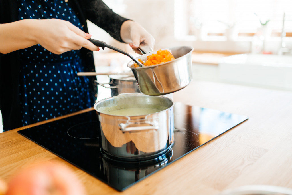 Organic meal being made in modern kitchen on induction cooktop