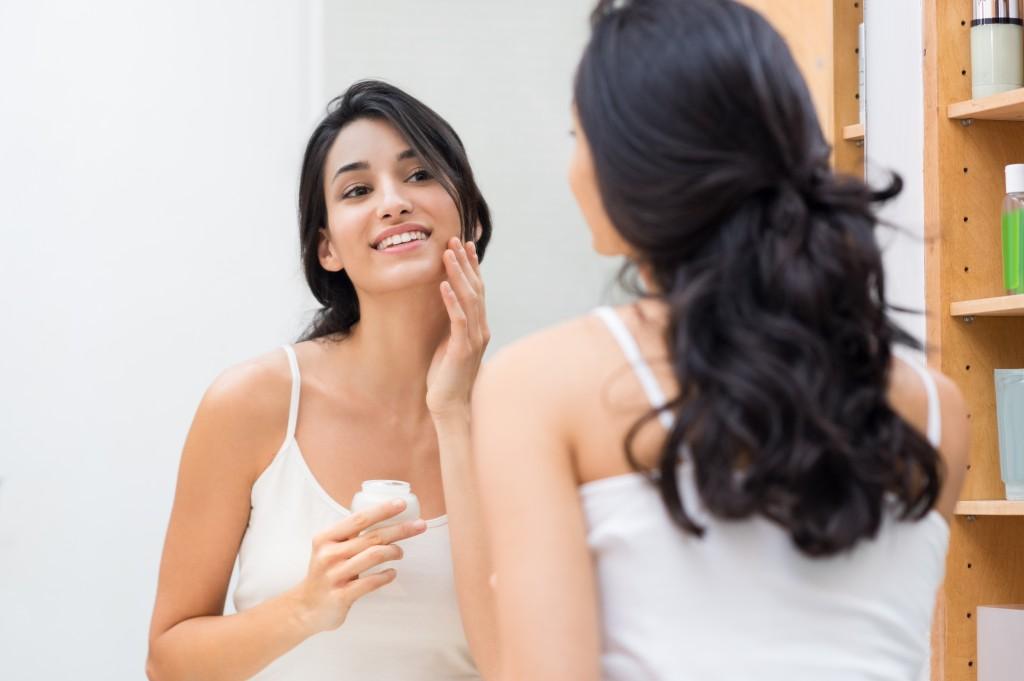 woman putting face moisturizer